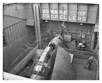 One of 850 squadron Avengers on the forward lielevator about to be raised to flight deck level. Note the man stood on the lift; the controls are visible in the open panel by his feet. February 17th 1944. Photo:   CFB Esquimalt Naval & Military  Museum, VR995.30.11