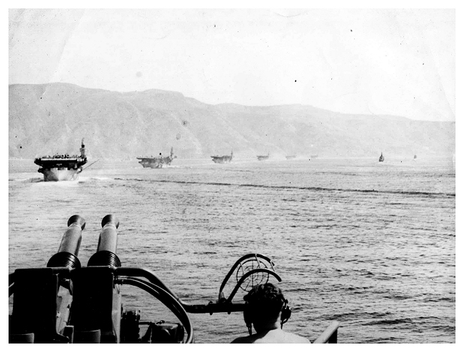 Seven Royal Navy escort carriers operated in the Mediterranean and the Aegean: H.M. Ships Attacker, Emperor, Huller, Khedive, Pursuer, Searcher, and Stalker, all are in line astern behind Emperor in this shot. Photo: Jack Price via Carl Berrington