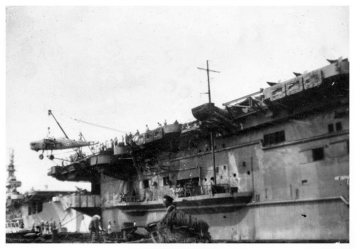 HMS Queen loading Barracuda fuselages in Colombo Harbour January 1946; HMS Patroller is moored behind her. The aircraft are for dumping at sea.