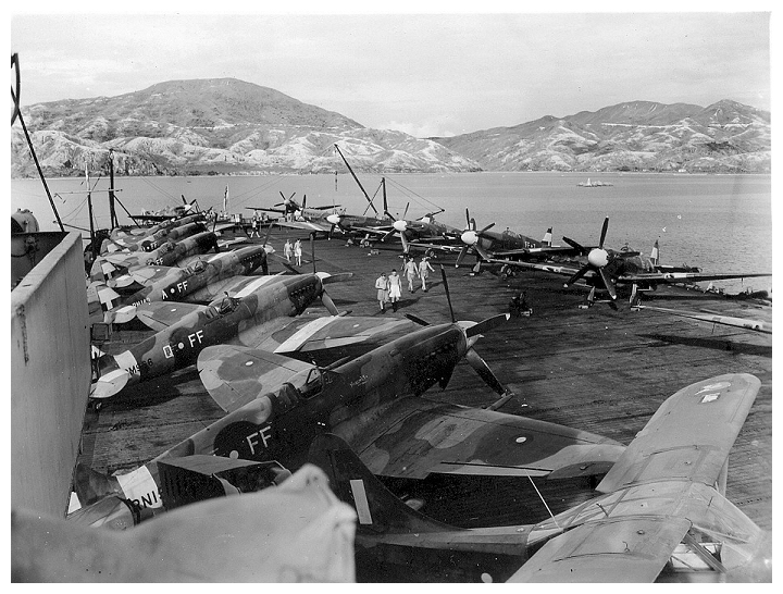 Spitfire Mk.XIVs of No 132 (City of Bombay) Squadron RAF aboard SMITER in Hong Kong Harbour, September 1945. There is also a single Stinson Reliant communications aircraft (nearest camera).   Photo: Courtesy of Terry Oxley