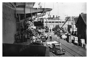 HMS Slinger alongside in Hong Kong unloading food and medical supplies for the colony.  Photo: Courtesy of E.C. McCarthy