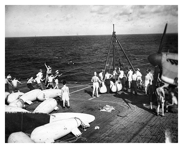 Loading spare drop tanks while anchored in San Pedro Bay, Leyte Gulf.  Photo: Courtesy of David Yates