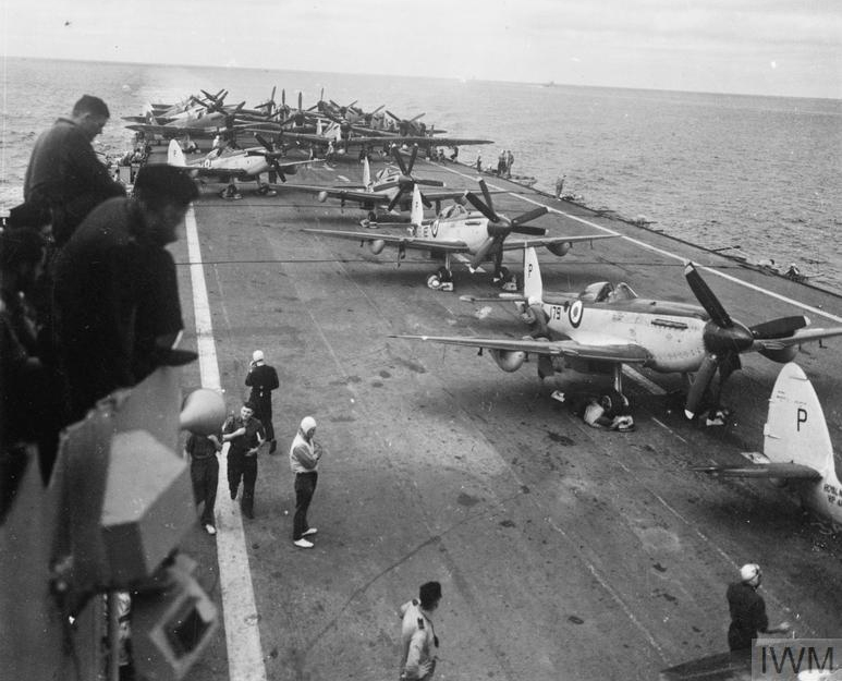 HMS TRIUMPH under way with Seafires and Fireflies parked on her flight deck.